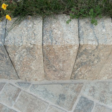 Grau schwarze Steinmauer als Beetabgrenzung