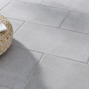 Terrassenplatte GABANO glatt von GODELMANN. Gepflasterter Steinboden in sandgrau und dunkel und geflochtener Tisch aus Bast mit offenem Buch