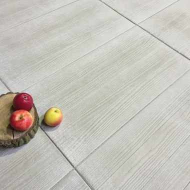 Terrassenplatte GABANO in Holzoptik von GODELMANN. Gepflasterter Steinboden in hellem sandgrau und in Holzoptik und Baumstumpf mit Aepfeln