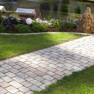 Gepflasterter Gartenweg mit Steinen in Muschelkalk Optik im Mehrsternsystem und Wiese und Gras und bepflanztes Beet mit Blumen und Rasen
