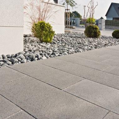 Grau gepflasterte Terrasse aus Sichtbetonplatten mit grauen Kieselsteinen und Buchsbaeumen und weiße Hauswand