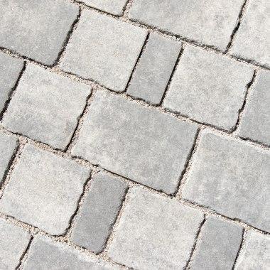 Gepflasterter Steinboden in grau schwarz im Mehrsteinsystem und weißen Kieselsteinen in den Zwischenraeumen