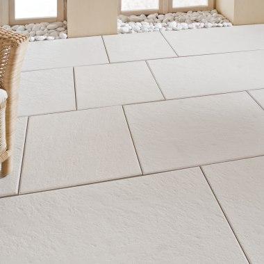Terrasse mit weissen Terrassenplatten in 80x40 cm mit geflochtenem Stuhl und Decke