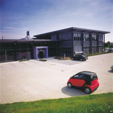 Gepflasterte Parklplaetze und Einfahrt vor Gebauede mit geparkten Autos und bepflanzten Rindenmulchbeeten und Jealosie und lila gestrichener Eingang