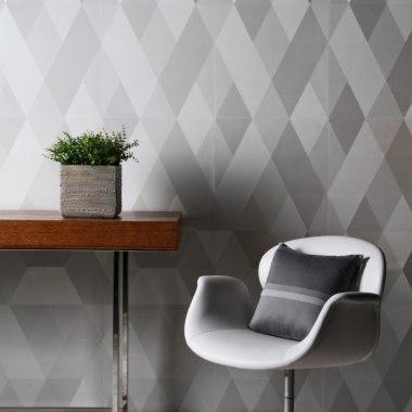 Wandverkleidung aus Sichtbeton mit Rauten in verschiedenen Grautoenen und hellgrauem Stuhl und dunkelgrauem Kissen und Sideboard aus Holz mit Edelstahlfuessen und Blumentop in hellgrau und Pflanze