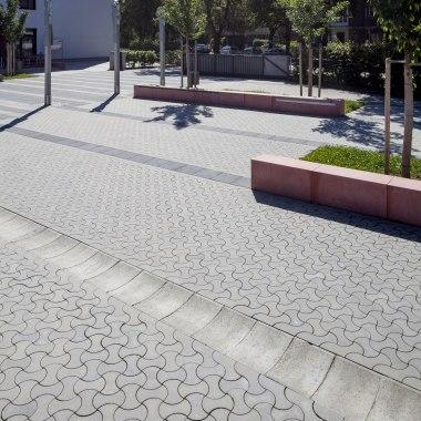 Hellgrau gepflasterter Parkplatz mit Steinen in dynamischer Optik und dunkelgrauer Parkabgrenzung und roter Sitzbank us Stein und Wiese und Baum