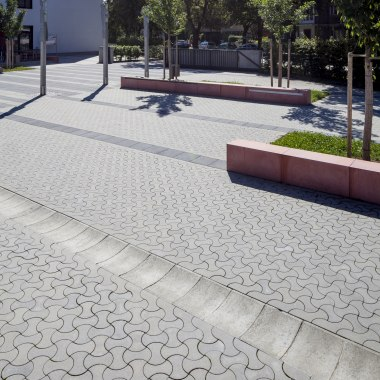 Pflasterstein SINUS von GODELMANN. Hellgrau gepflasterter Parkplatz mit Steinen in dynamischer Optik und dunkelgrauer Parkabgrenzung und roter Sitzbank us Stein und Wiese und Baum