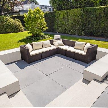 Terrasseneinfassung aus grauem Sichtbeton die eine graugepflasterten Terrassenboden aus Pflasterstein mit Loungemoebel und Auflagen und Kissen einrahmt und Wiese und Lichter und Baeume und Hecke und Kieselsteine