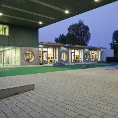 Vorplatz mit grossen grauen quadratischen Steinplatten mit grünem Rasen und graues Gebäude bei Daemmerung