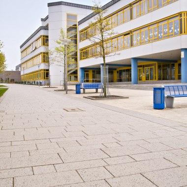 Vorplatz mit laenglichen beigen und sandsteinfarbenen Steinplatten und Gebaeude mit Glasfront und Wiese und blaue Sitzbaenke