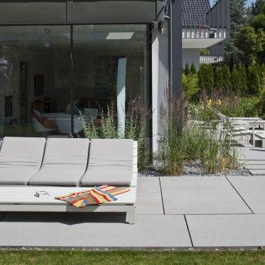 Terrassenboden aus grossen laenglichen hellgrauen Steinplatten aus Beton und Haus mit Glasfassade und Terrasse mit Liegestuehlen und Garten mit Pflanzen und Baeumen und Loungemoebeln und gruene Rasenflaechen und Gartenweg aus laenglichen grauen Steinplatt