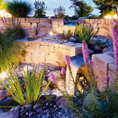 Idyllischer Garten mit beiger Sandsteinmauer mit Bachlauf und mit Graesern und Pflanzen bepflanztes Kieselbeet und Himmel und Stuhl