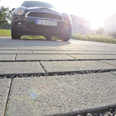 Gepflasterter Parkplatz mit anthrazit Rasenliner und Basalt Splitt in den Zwischenraeumen und geparkter Auto Mini und Wiese und Pflanzen und Sonnenschein