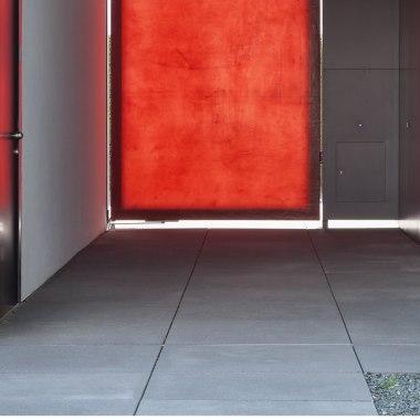 Großformatige Platten aus Großformatsteinen vor halbtransparentem rotem Eingangs Tor und weißem modernem Haus