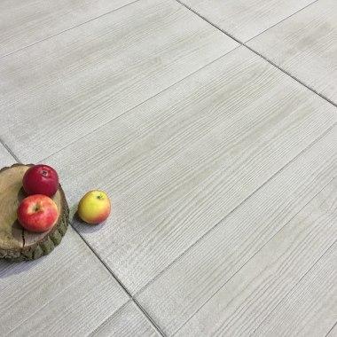 Gepflasterter Steinboden in hellem sandgrau und in Holzoptik und Baumstumpf mit Aepfeln